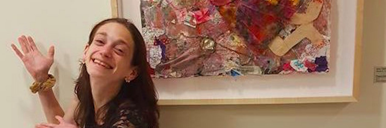 young woman posing with her painting