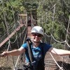 woman standing on swinging bridge wearing helmet