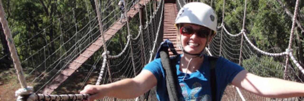 woman standing on swinging bridge wearing helmet