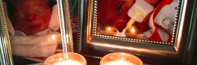 Two framed photos of babies with lit candles in front of each