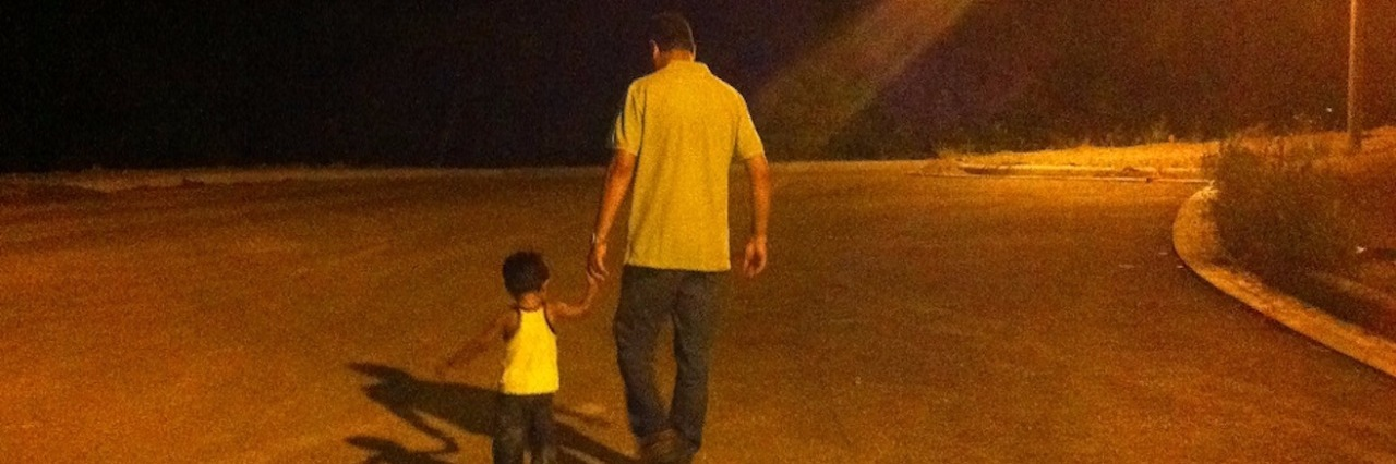 dad and son walking hand in hand