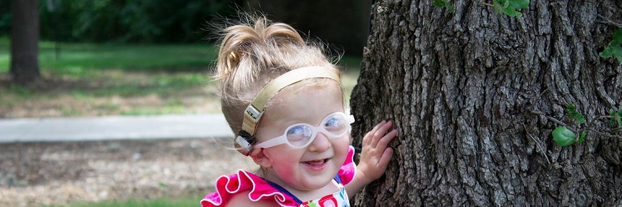 Ashlyn near a tree outside smiling.