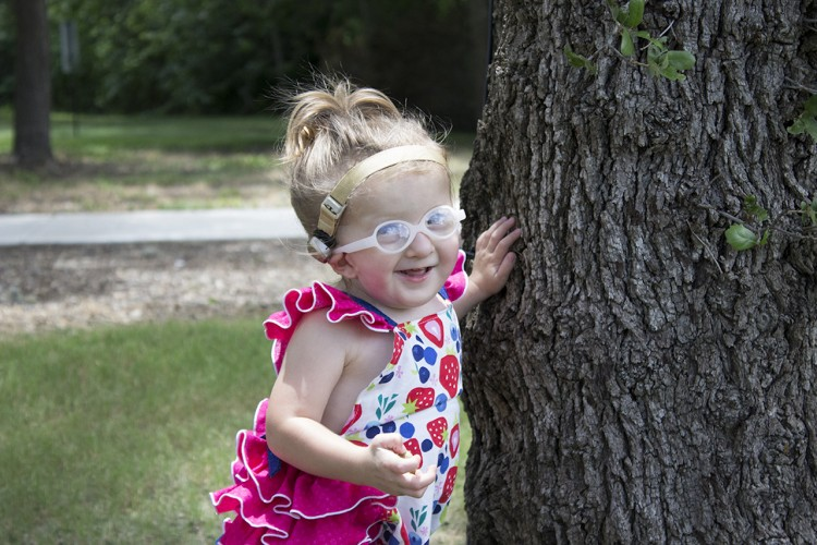 Ashlyn near a tree outside smiling.