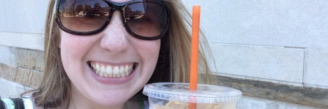 girl wearing sunglasses and holding coffee cup