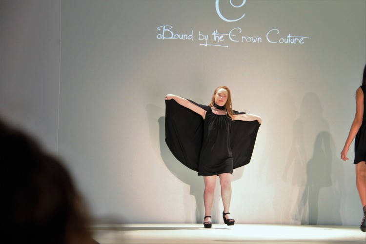 Madeline Stuart on the runway with her cape open