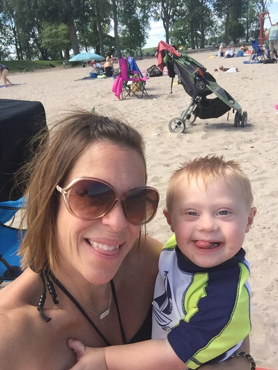 mom and little boy with down syndrome smiling at the beach
