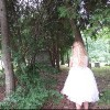 woman wearing white dress walking under trees