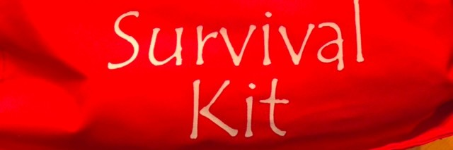 "red bag that says ""survival kit"""
