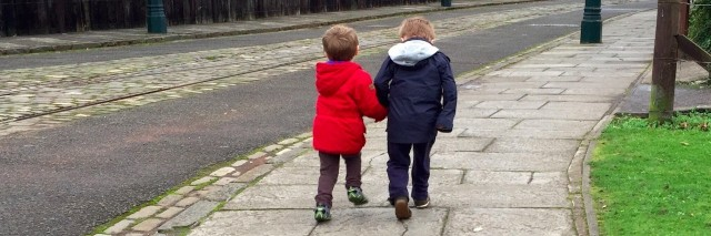 Two children walking on a sidewalk