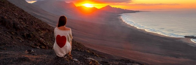 woman watches sunset while sitting on a mountain