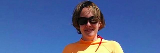 woman on a beach holding a bodyboard