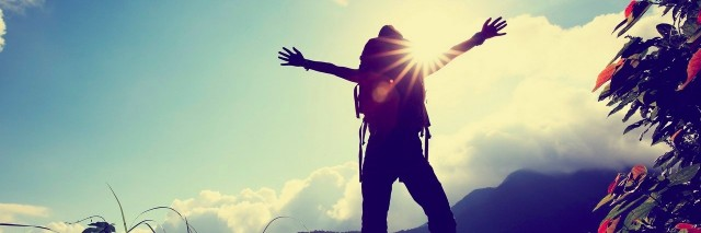 hiker open her arms on mountain peak at sunrise