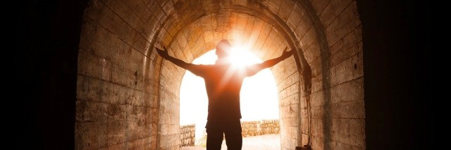 Man stands inside of dark tunnel with sun shining in