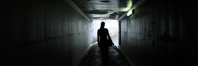 woman walking out of a dark tunnel