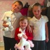 Three kids wearing school uniforms, two of them holding stuffed animals