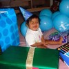 Little boy at birthday party surrounded by gifts and balloons