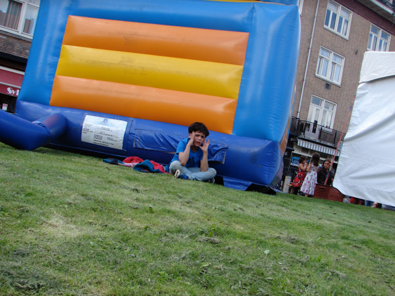 little boy sitting outside a bouncy house