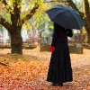 a woman dressed for a funeral holding an umbrella standing in a grave yard.