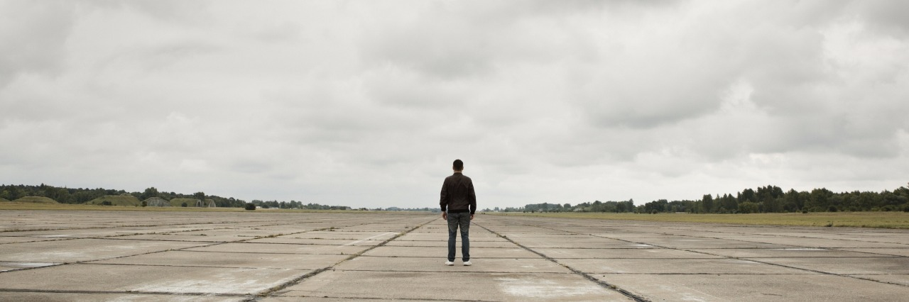 man standing along in the middle of a runway
