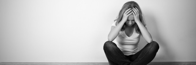 girl sitting on floor with head in hands