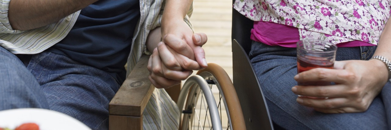 Couple with woman in wheelchair holding hands.