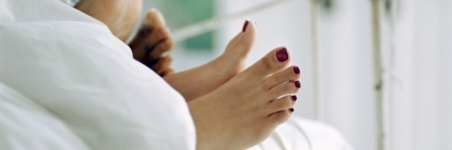 Couple lying in bed, feet sticking out of covers, low section