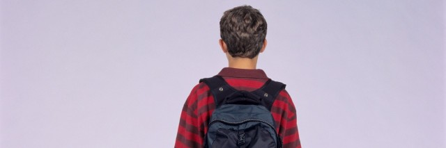 Teenage boy (14-15) with rucksack, posing in studio