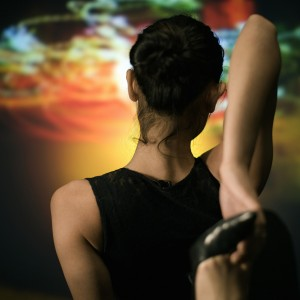 Young woman stretching, rear view, fire projected in background