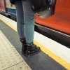 woman wearing boots waiting for metro train