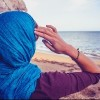 Rear view of woman with headscarf sitting on the beach by a rock and looking at the sea