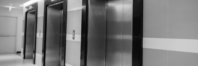 black and white photo of three elevators side by side