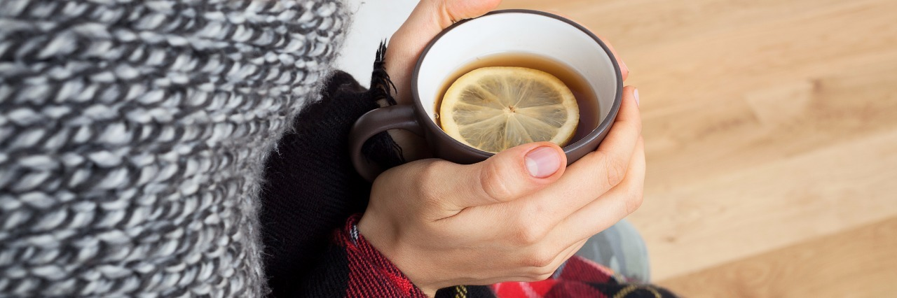 woman who got cold sitting in scarf and blanket holding a cup of tea