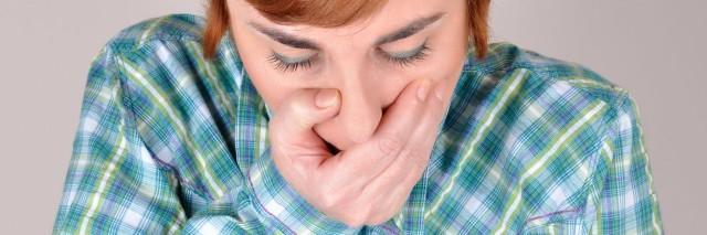 a woman in a plaid shirt holding her hand over her mouth
