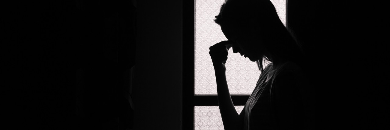 Depressed young woman in a dark room