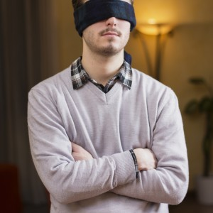 Blindfolded young man at home in living room