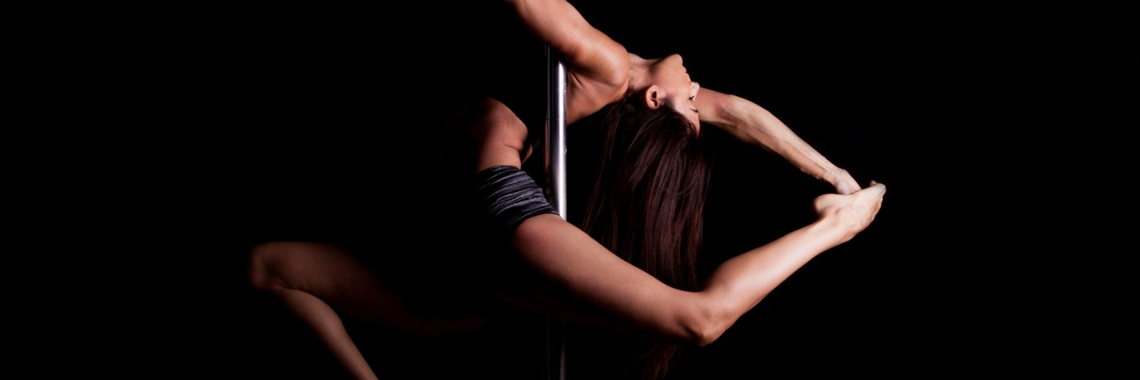 pole dancer in dark setting