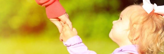 Mother holding hand of little daughter outdoors.