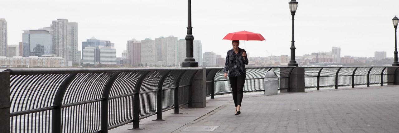 Woman walking on bridge, holding red umbrella