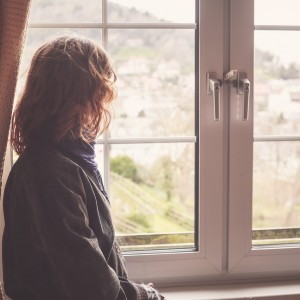Young woman is looking out the window