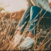 Defocused abstract loneliness concept. Cropped feet of lonely young woman sitting on stone. Solitude
