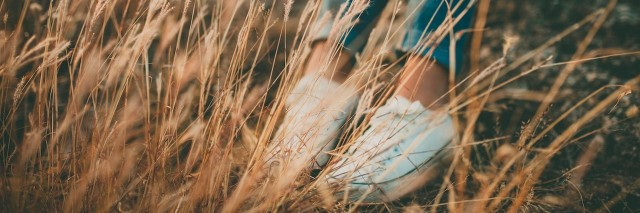 woman sitting in a field of tall grass