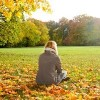 lonely young woman sitting in autumn park, rear view