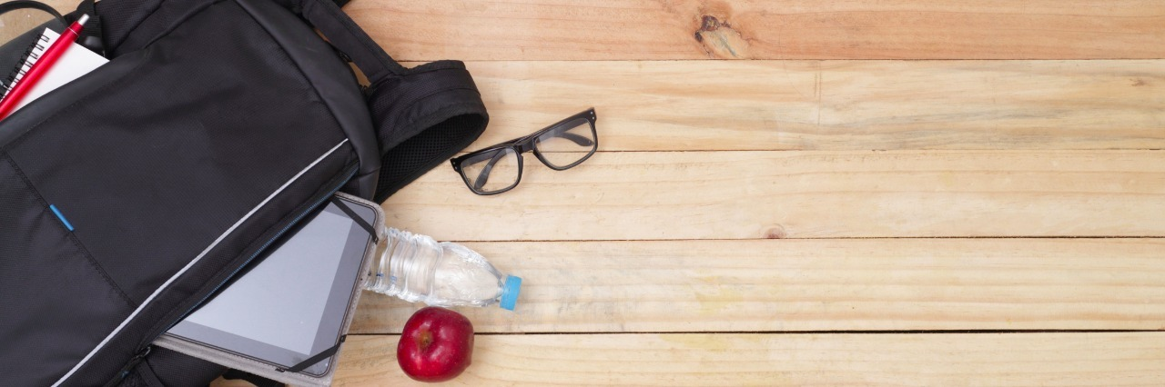 Backpack next to red shoes and glasses on a wood floor