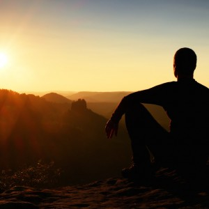man watching sunrise on mountaintop