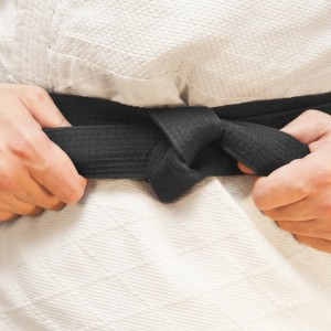 person wearing a taekwondo outfit and tightening their black belt