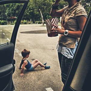 child sitting in parking lot next to mom's car