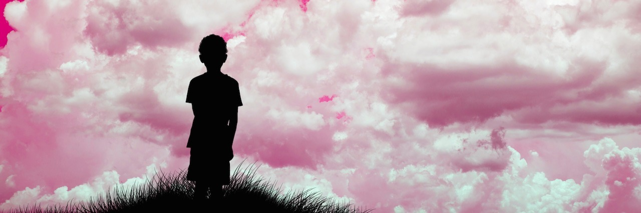 silhouette of boy looking at pink sky
