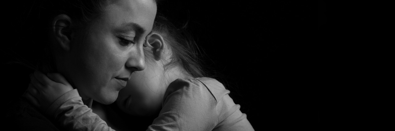 black and white picture of a mother holding her child against her chest in front of a black background