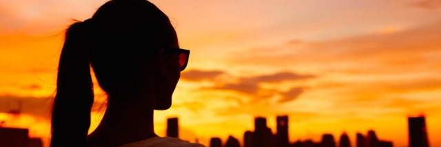 silhouette of woman looking at sunset over city skyline