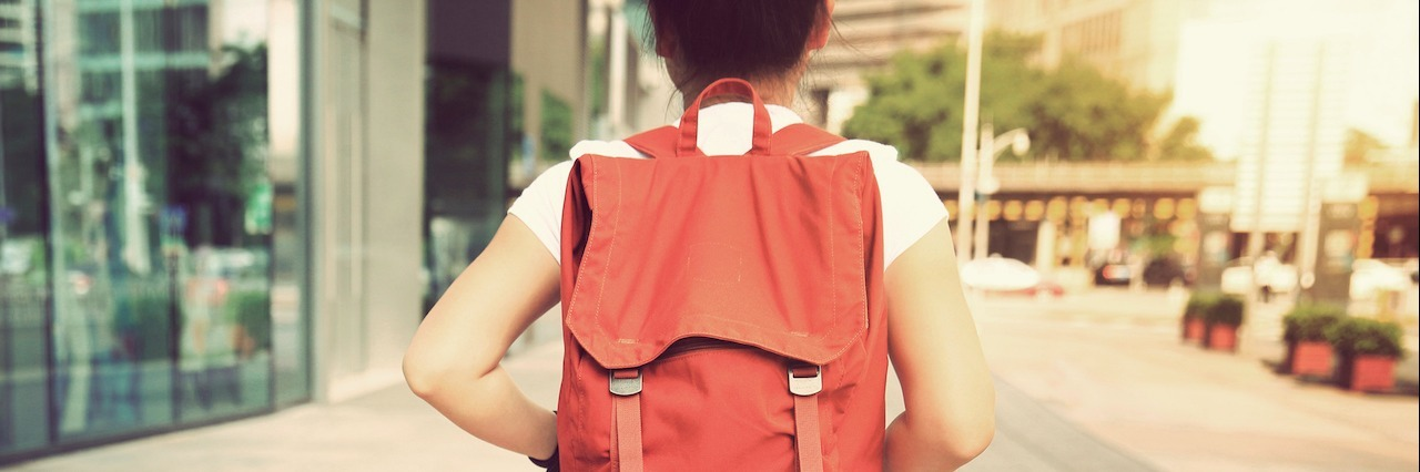 woman walking down street wearing orange backpack
